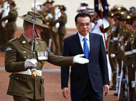 Chinese Premier Li Keqiang inspects an honour guard during an official welcoming ceremony at Parliament House in Canberra