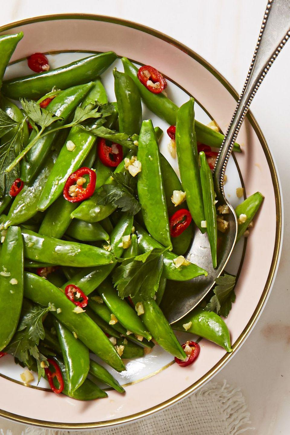 """<p>Sweet snap peas are loaded with garlic and chile for even more flavor.</p><p><em><a href=""""https://www.goodhousekeeping.com/food-recipes/a43686/spicy-sesame-sugar-snaps-recipe/"""" rel=""""nofollow noopener"""" target=""""_blank"""" data-ylk=""""slk:Get the recipe for Spicy Sesame Sugar Snaps »"""" class=""""link rapid-noclick-resp"""">Get the recipe for Spicy Sesame Sugar Snaps »</a></em></p>"""