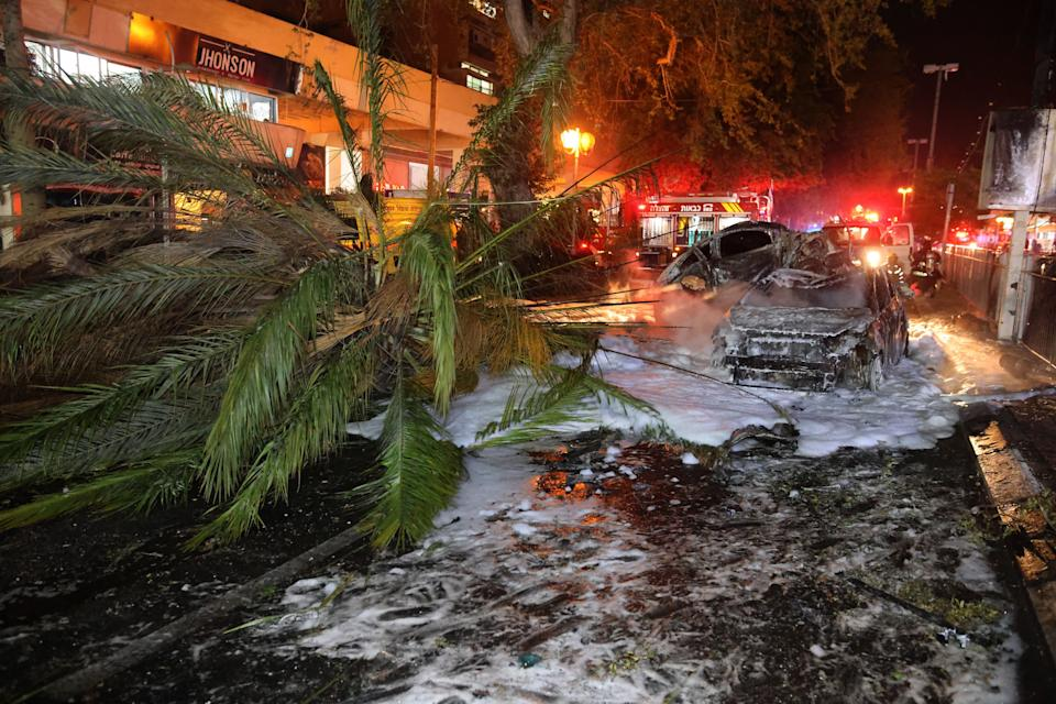 Israeli firefighters extinguish burning cars in the town of Holon near Tel Aviv, on May 11, 2021, after rockets were launched towards Israel from the Gaza Strip controlled by the Palestinian Hamas movement. (Photo by Ahmad GHARABLI / AFP) (Photo by AHMAD GHARABLI/AFP via Getty Images) (Photo: AHMAD GHARABLI via Getty Images)
