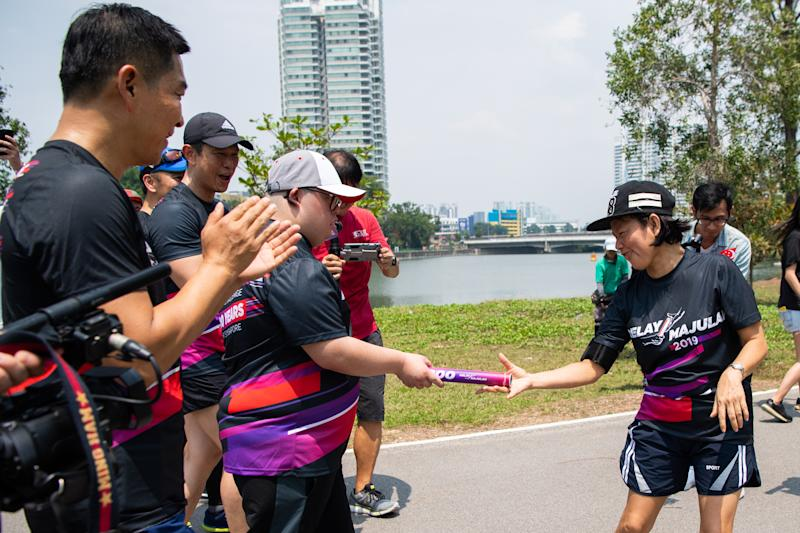 Relay Majulah runner Ong Jin Kian (left) hands over the baton to Oh Siew May in the first leg of the nine-day, 2,000km relay. (PHOTO: Relay Majulah)