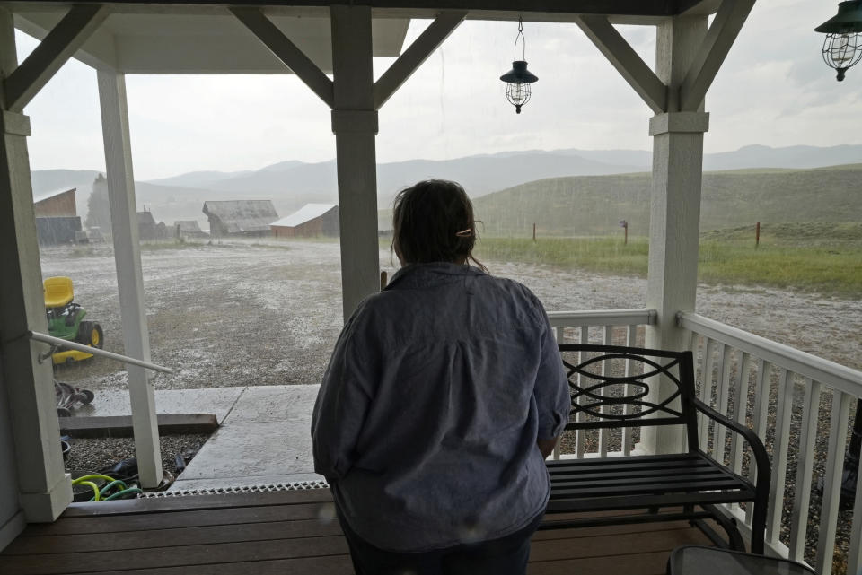 Jo Stanko, who along with her husband, Jim Stanko, are third-generation cattle ranchers, watches a sudden afternoon rainstorm, Wednesday, July 14, 2021, on their ranch near Steamboat Springs, Colo. Due to extreme drought conditions this year, Jim Stanko says he may have to sell some of their herd if he can't harvest enough hay to feed them. (AP Photo/Brittany Peterson)