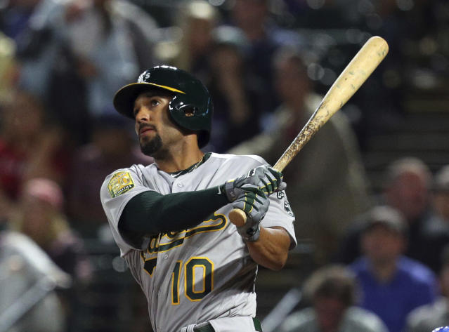 Oakland Athletics Marcus Semien (10) watches his home run shot against the Texas Rangers that broke the tie in the ninth inning of a baseball game Monday, April 23, 2018, in Arlington, Texas. (AP Photo/Richard W. Rodriguez)