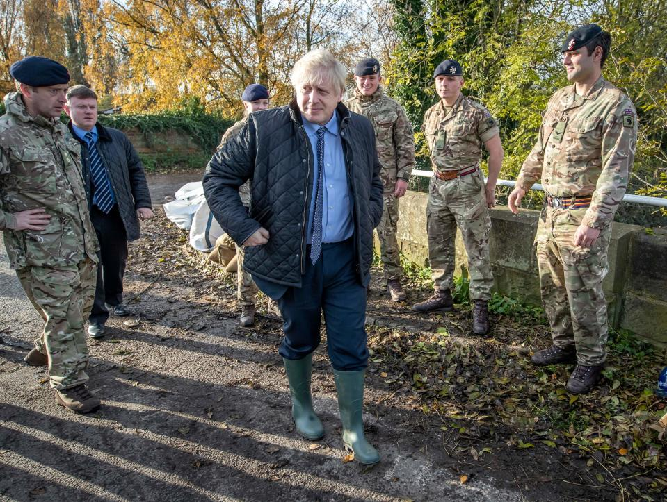 Britain's Prime Minister Boris Johnson walks past members of the Light Dragoons during a visit to Stainforth near Doncaster, northern England, on November 13, 2019, following flooding caused by days of heavy rain, and the River Don bursting its banks. (Photo by Danny Lawson / POOL / AFP) (Photo by DANNY LAWSON/POOL/AFP via Getty Images)