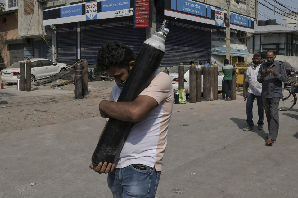 A man walks carrying a refilled cylinder as family members of Covid-19 patients wait in queue to refill their oxygen cylinders at Mayapuri area in New Delhi, India.