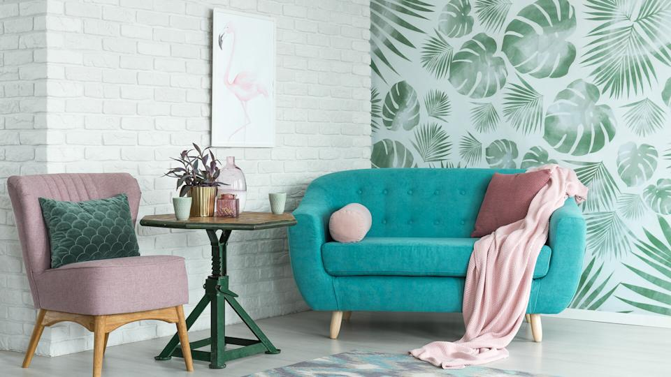 Green table with plant between pink chair and blue sofa in floral living room with wallpaper and poster.