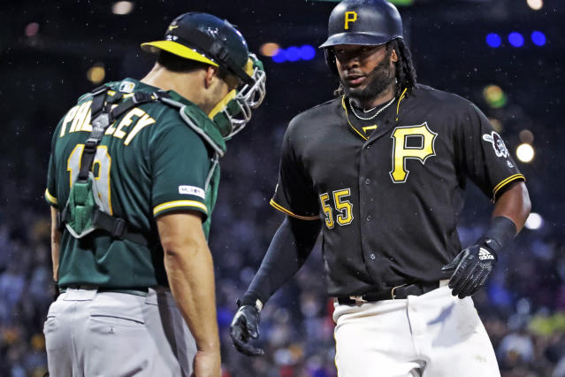 Pittsburgh Pirates' Josh Bell (55) crosses home plate in front of Oakland Athletics catcher Josh Phegley after hitting a two-run home run off starting pitcher Chris Bassitt during the third inning of a baseball game in Pittsburgh, Saturday, May 4, 2019. It was Bell's second home run of the game. (AP Photo/Gene J. Puskar)