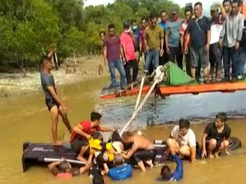 Members of the public attempting to aid victims from a four-wheel-drive that rolled off a ferry in Triso wharf in Beladin January 1, 2020.