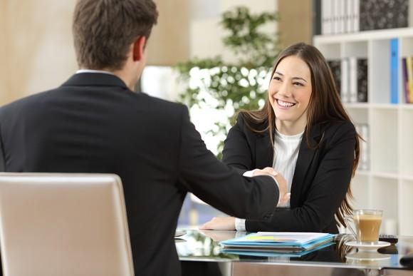 Smiling businesswoman shakes hands with businessman.