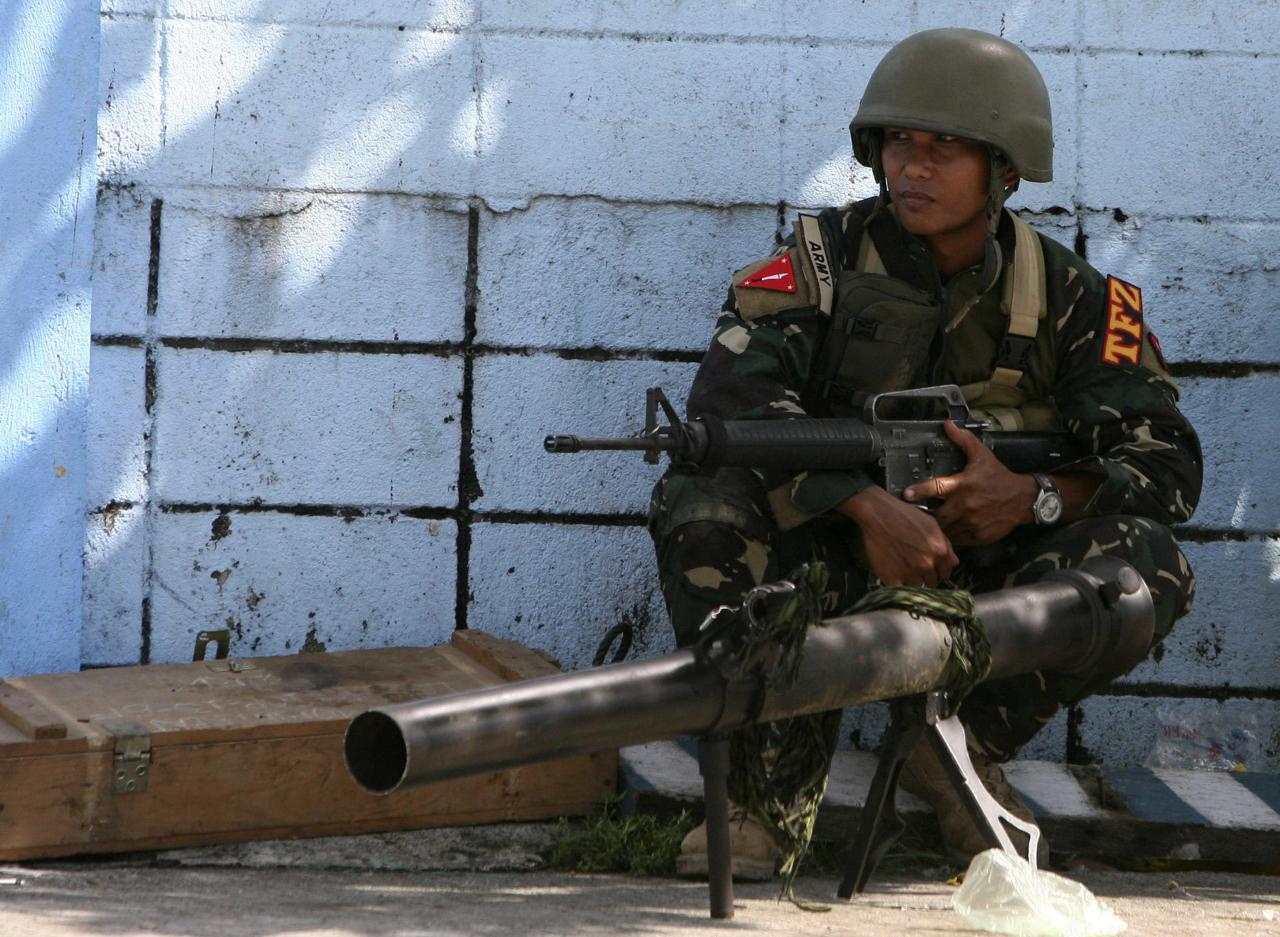 A government soldier squats next to a 90RR shoulder-fired rocket launcher while awaiting orders after Muslim rebels members of the Moro National Liberation Front (MNLF) occupied villages in Zamboanga city, southern Philippines September 9, 2013. Muslim rebels took 30 civilian hostages in the southern Philippines on Monday and held security forces in a standoff as part of a drive to derail peace talks, officials said. Police commandos cordoned off parts of Zamboanga City on the island of Mindanao after a rogue faction of the MNLF took hostages and tried to march to the city hall to raise their flag, an army commander said. REUTERS/STRINGER (PHILIPPINES - Tags: POLITICS MILITARY CIVIL UNREST)