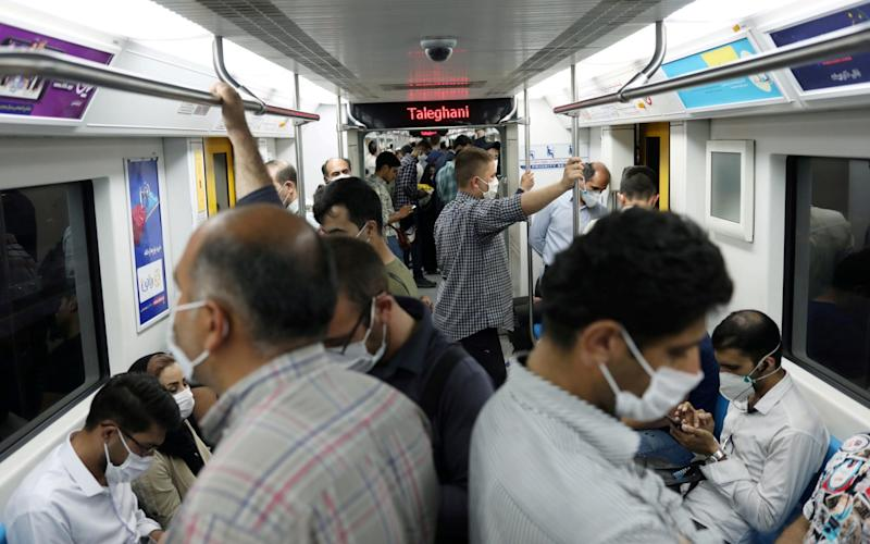 Iranians wearing protective face masks ride the metro, following a steady increase in cases in the country - Wana News Agency