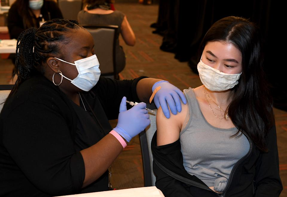 LAS VEGAS, NEVADA - JANUARY 12:  UNLV Medicine medical assistant Delicia Sullivan (L) administers a Pfizer-BioNTech COVID-19 vaccination to UNLV School of Nursing student Arianna Nicole at UNLV on January 12, 2021 in Las Vegas, Nevada. UNLV officials established the vaccination center on campus yesterday and plan to open another one next week at College of Southern Nevada in Henderson, Nevada, to distribute about 1,000 doses a week at each location to the Nevada System of Higher Education (NSHE) schools. The first vaccinations are going to front-line health care staff, including members of the UNLV medical, dental and nursing schools, people who see patients and university police officers. After that, plans are to vaccinate employees who work on campus, remaining NSHE staff and students living in on-campus housing, followed by the remaining student body and possibly the public.  (Photo by Ethan Miller/Getty Images)