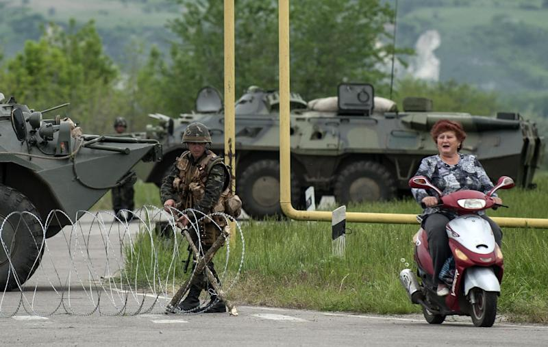 A woman rides a scooter passing a Ukrainian army checkpoint on the main road to Spivakovka village in the eastern Ukraine, 60km (36 miles) outside in Luhansk, Ukraine, Monday, May 12, 2014. Pro-Moscow insurgents in eastern Ukraine declared independence Monday and sought to join Russia, undermining upcoming presidential elections, strengthening the Kremlin's hand and putting pressure on Kiev to hold talks with the separatists following a referendum on self-rule. (AP Photo/Evgeniy Maloletka)