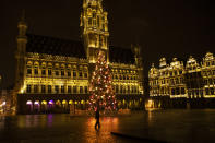 A man walks along a virtually empty Grand Place square during a curfew in downtown Brussels, Thursday, Dec. 31, 2020. As the world says goodbye to 2020, there will be countdowns and live performances, but no massed jubilant crowds in traditional gathering spots like the Champs Elysees in Paris and New York City's Times Square this New Year's Eve. The virus that ruined 2020 has led to cancelations of most fireworks displays and public events in favor of made-for-TV-only moments in party spots like London and Rio de Janeiro. (AP Photo/Francisco Seco)