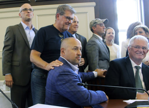 University of Connecticut men's basketball coach Dan Hurley, left, women's basketball coach Geno Auriemma, second from left, and athletic director David Benedict, seated foreground, watch the board of trustees vote on Wednesday, June 26, 2019, on the school's campus in Storrs, Conn., to move most of UConn's athletic teams from the American Athletic Conference to the Big East. (AP Photo/Pat Eaton-Robb)