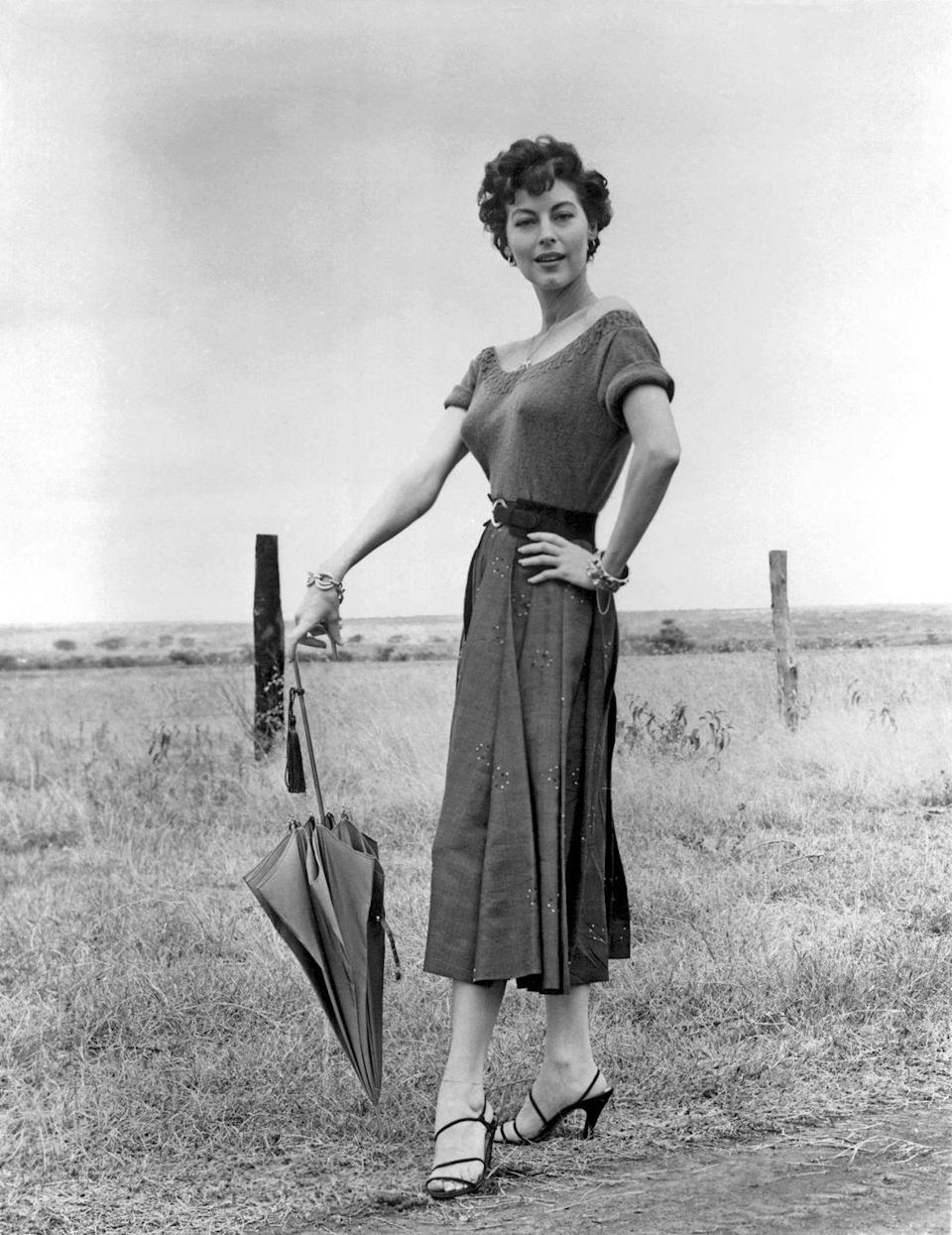 <p>Gardner poses jauntily with an umbrella in Africa while filming director John Ford's <em>Mogambo</em> and wears a sweater with rolled sleeves, full skirt, and—always the lady—a pair of heels.</p>