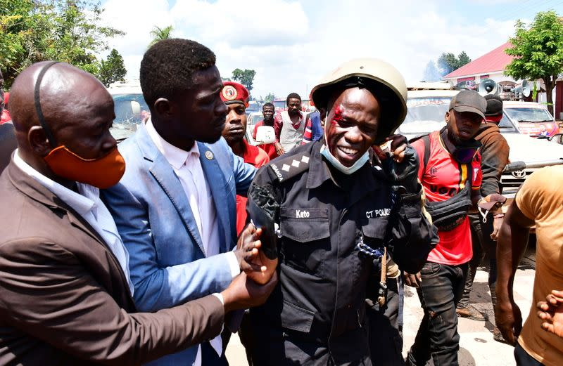 Ugandan pop star and presidential candidate Bobi Wine assists one of his bodyguards who was injured in clashes near Kampala