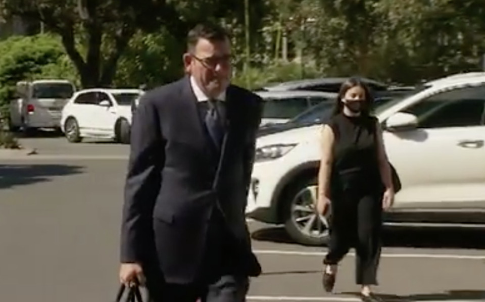 Mr Andrews as he walks to parliament without a mask.