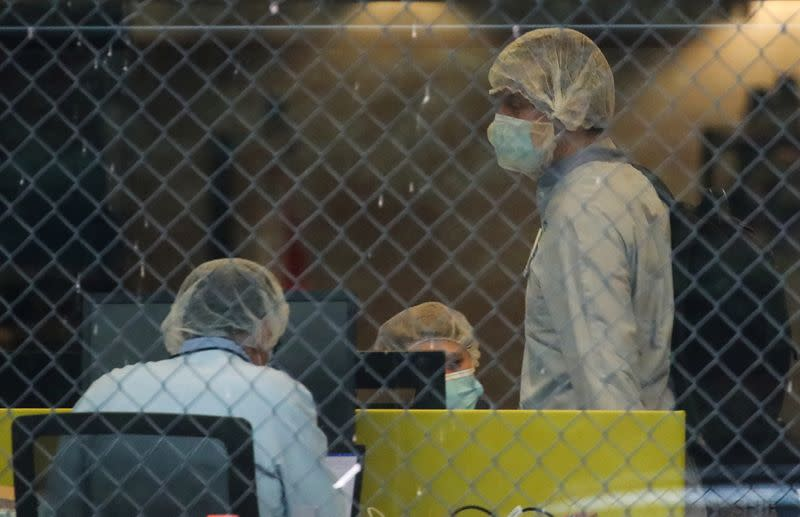 People wearing protective face masks are seen inside the Pfizer plant in Puurs