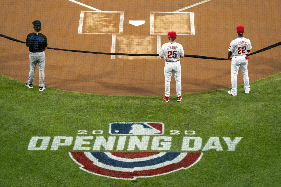 Miami Marlins manager Don Mattingly, left, Philadelphia Phillies manager Joe Girardi, center, and Andrew McCutchen, right, hold a black ribbon in support of the Black Lives Matter movement prior to a baseball game Friday, July 24, 2020, in Philadelphia. (AP Photo/Chris Szagola)