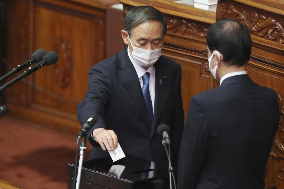Yoshihide Suga, left, drops his ballet in a parliamentary vote at the parliament's lower house in Tokyo, Wednesday, Sept. 16, 2020. Suga was formally elected Wednesday as Japan's new prime minister in the vote, replacing Shinzo Abe. (AP Photo/Koji Sasahara)