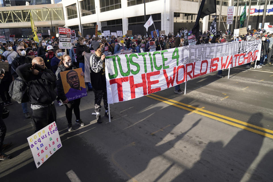 Demonstrators gather outside the Hennepin County Government Center, Monday, March 8, 2021, in Minneapolis where the trial for former Minneapolis police officer Derek Chauvin began with jury selection. Chauvin is charged with murder in the death of George Floyd during an arrest last May in Minneapolis. (AP Photo/Jim Mone)
