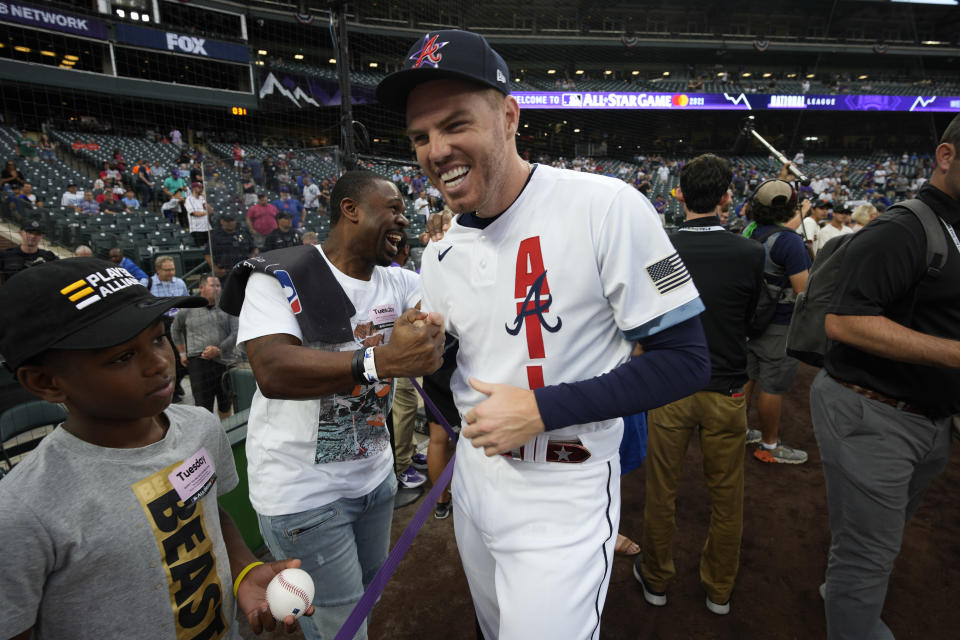 National League's Freddie Freeman, of the Atlanta Braves, laughs with former player Michael Bourn during batting practice prior to the MLB All-Star baseball game, Tuesday, July 13, 2021, in Denver. (AP Photo/David Zalubowski)