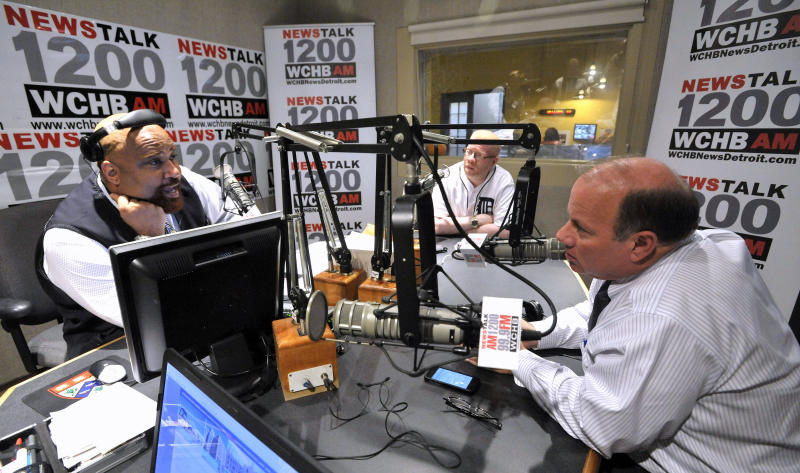 """In this Oct. 16, 2013 photo, Detroit Mayoral Candidate Mike Duggan, right, and his guest Impact Church Pastor Keenan Knox, center, talk with radio host Angelo Henderson, left, during a break on Henderson's show called, """"Your Voice."""" A medical examiner's spokesman said Henderson, Pulitzer prize-winning Detroit journalist, radio host and co-founder of a prominent community patrol group, died Saturday, Feb. 15, 2014. (AP Photo/Detroit News, Todd McInturf) DETROIT FREE PRESS OUT; HUFFINGTON POST OUT"""