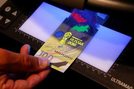 FILE PHOTO: General Director of Goznak state firm Arkady Trachuk shows security features of the newly designed 100-rouble banknote dedicated to the 2018 FIFA World Cup, during a news conference in Moscow, Russia May 22, 2018. REUTERS/Sergei Karpukhin/File Photo