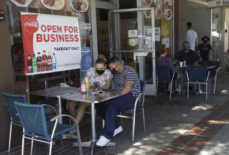 FILE - In this July 18, 2020, file photo, Josefina Pacheco, front left, and her husband Norberto wait to have a meal served outside at a restaurant in Burbank, Calif. Los Angeles County announced new coronavirus-related restrictions Sunday, Nov. 22, 2020, that will prohibit in-person dining for at least three weeks as cases rise at the start of the holiday season and officials statewide begged Californians to avoid traveling or gathering in groups for Thanksgiving. The new restrictions in Los Angeles County, the nation's most populous, came as the California Department of Health and Human Services reported more than 15,000 coronavirus cases statewide Saturday, by far the highest level since the pandemic began in March. Another 14,000 cases were recorded Sunday. (AP Photo/Marcio Jose Sanchez, File)