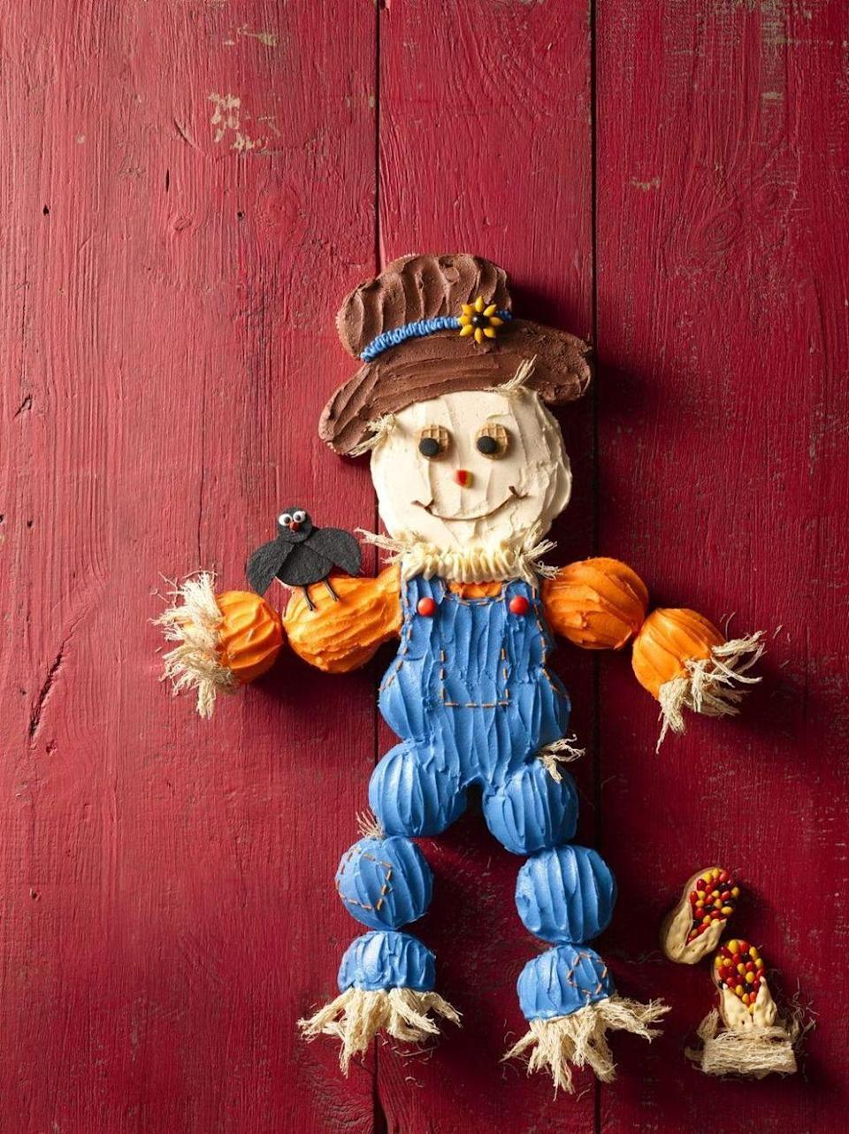 """<p>There's nothing scary about this scarecrow. Use cupcakes to make this giant, colorful creation that's much easier to distribute come serving time. </p><p><em><a href=""""https://www.womansday.com/food-recipes/food-drinks/recipes/a56159/cupcake-scarecrow-recipe/"""" rel=""""nofollow noopener"""" target=""""_blank"""" data-ylk=""""slk:Get the recipe for Scarecrow Cupcakes Cake."""" class=""""link rapid-noclick-resp"""">Get the recipe for Scarecrow Cupcakes Cake.</a></em></p>"""