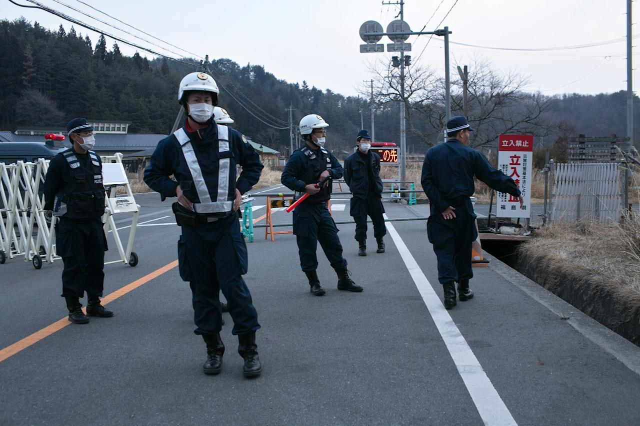 NAMIE, JAPAN - MARCH 08:  Policemen stand at checkpoint in the village of Tsushima on March 8, 2013 in Namie, Fukushima Prefecture, Japan. Japan is preparing to commemorate the second anniversary of the magnitude 9.0 earthquake and subsequent tsunami that claimed more than 18,000 lives.  (Photo by Ken Ishii/Getty Images)