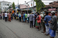 People line up to receive free meal distributed by a voluntary organization during relaxation hours of a lockdown put in place to curb the spread of coronavirus pandemic in Kolkata, India, Wednesday, June 16, 2021. (AP Photo/Bikas Das)