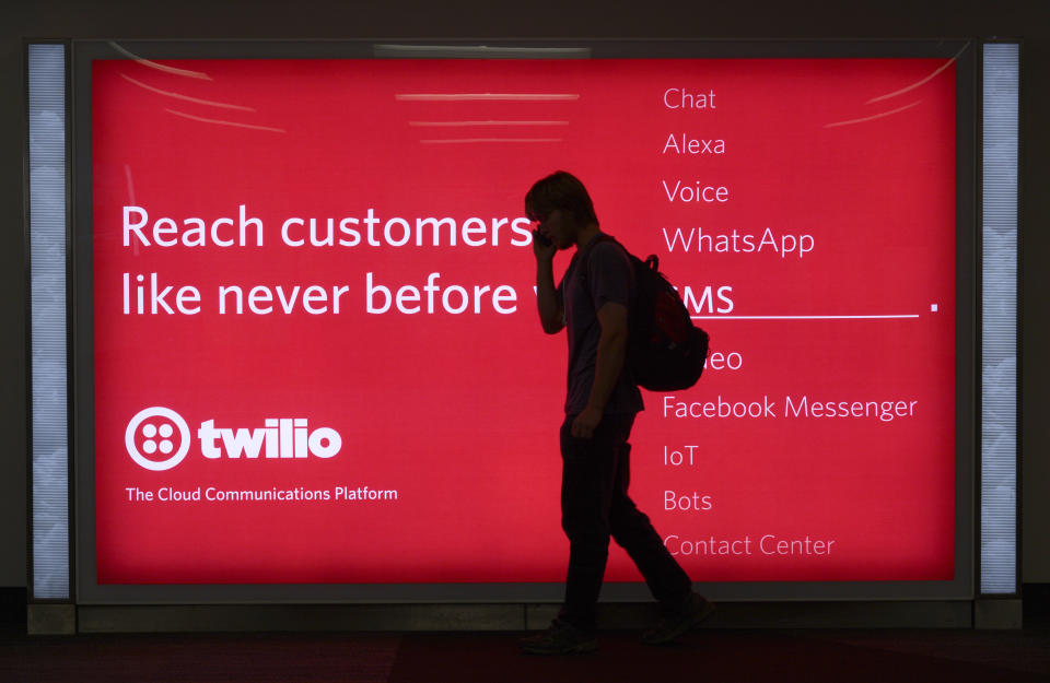 SAN FRANCISCO, CALIFORNIA - SEPTEMBER 17, 2018:  A passenger waiting to board his plane walks in front of a sign advertising Twilio at San Francisco International Airport in San Francisco, California. Twilio is a cloud communications platform based in San Francisco. (Photo by Robert Alexander/Getty Images)