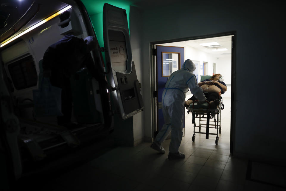 A healthcare worker pushes a woman who is suspected of having COVID-19 into Llavallol Dr. Norberto Raúl Piacentini Hospital in Lomas de Zamora, Argentina, Saturday, May 1, 2021. Doctors say they are seeing many younger patients, partly because youths are being infected with coronavirus variants at social gatherings, while older people are protected by vaccines they have received. (AP Photo/Natacha Pisarenko)