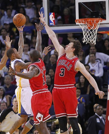 Golden State Warriors' Monta Ellis (8) takes a shot over Chicago Bulls' Omer Asik (3), from Turkey, and Ronnie Brewer (11) during the first half of an NBA basketball game Monday, Dec. 26, 2011, in Oakland, Calif. (AP Photo/Tony Avelar)