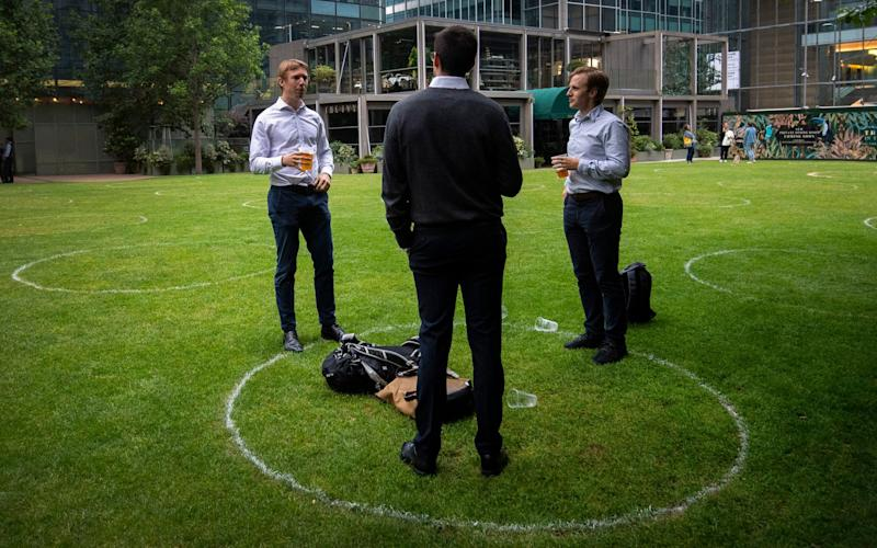 Drinkers stand within rings marked on the grass to maintain their social distance outside a bar in Canary Wharf, East London as further coronavirus lockdown restrictions are lifted in England - PA