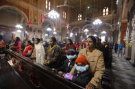 Indian Christians, some wearing face masks as a precaution against the coronavirus, attend a Christmas mass at St. Joseph's Cathedral in Prayagraj, India. Friday, Dec. 25, 2020. (AP Photo/Rajesh Kumar Singh)
