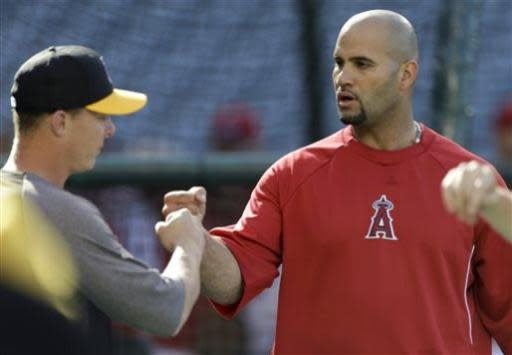 Los Angeles Angels designated hitter Albert Pujols, right, talks with Pittsburgh Pirates relief pitcher Ryan Reid before their baseball game in Anaheim, Calif., Friday, June 21, 2013. (AP Photo/Chris Carlson)