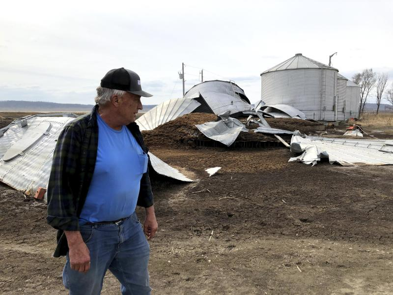This photo taken March 12, 2020, near Rock Port, Missouri, shows tenant farmer Phil Graves examining grain storage bins that were destroyed in a 2019 flood. Some of the land where Graves grows corn has been offered for sale to provide room for a levee to be rerouted so the Missouri River can roam more widely. Levee setbacks are among measures being taken in the U.S. heartland to control floods in ways that work with nature instead of trying to dominate it with concrete infrastructure. Graves says he'd prefer to keep cultivating the parcel but understands why the setback is needed. (AP Photo/John Flesher)