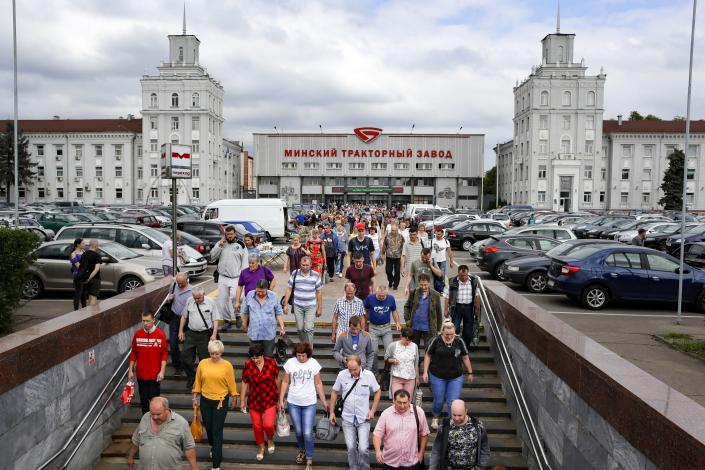 In this photo taken on Wednesday, Aug. 5, 2020, Employees leave the Minsk Tractor Plant after their shift in Minsk, Belarus. While Belarus didn't impose any quarantine measures or economic restrictions, its economy has been badly battered by the global pandemic. Moscow this year has also withdrawn a discount on oil supplies, which Belarus processed to export oil products, depriving Lukashenko's government of an estimated $700 million in lost annual revenues. (AP Photo/Sergei Grits)