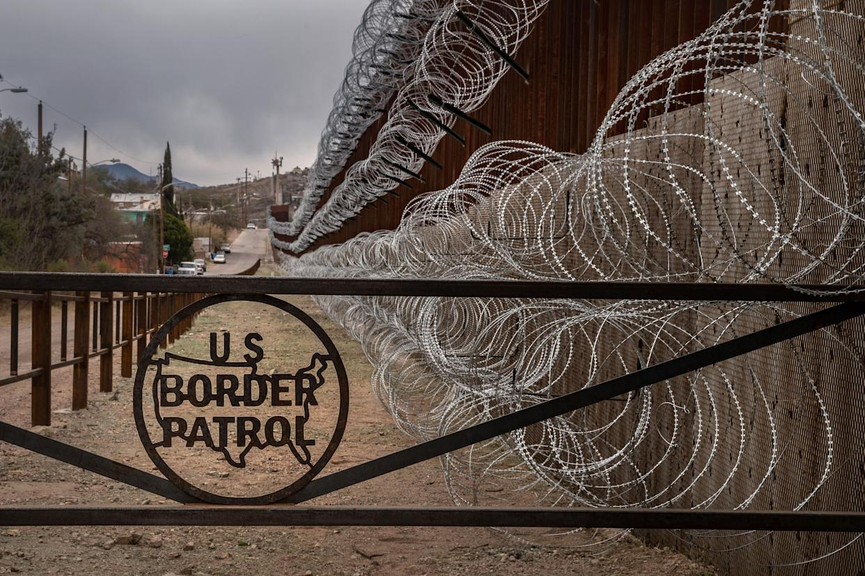 A metal fence marked with the U.S. Border Patrol insignia prevents people from getting close to the barbed/concertina wire covering the larger border fence in Nogales, Arizona, on Feb. 9, 2019. (Photo: ARIANA DREHSLER via Getty Images)