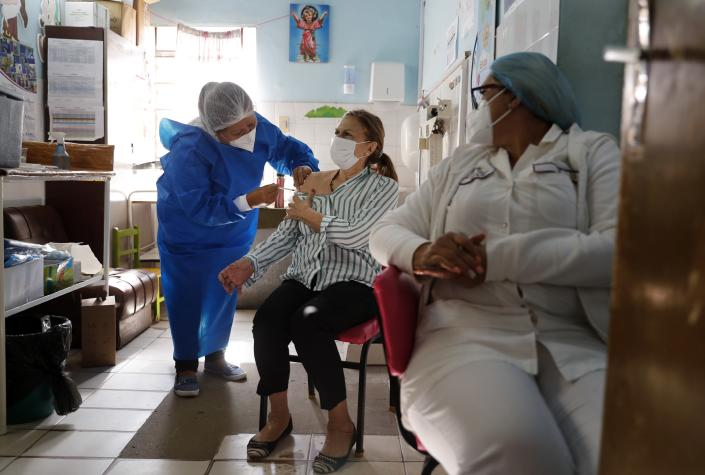 An elderly woman gets a shot of the Astra Zeneca vaccine for COVID-19 at Trinidad Maternity Hospital in Asuncion, Paraguay, Friday, April 30, 2021. People older than age 75 are being vaccinated. (AP Photo/Jorge Saenz)
