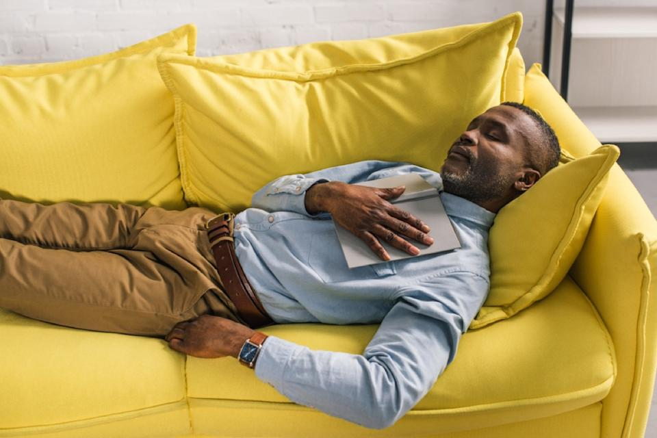 middle-aged man napping on yellow couch, ways to be a healthier man