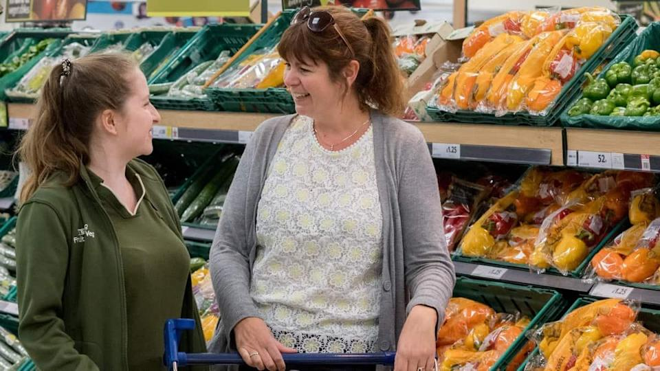 A Tesco employee chatting with a customer