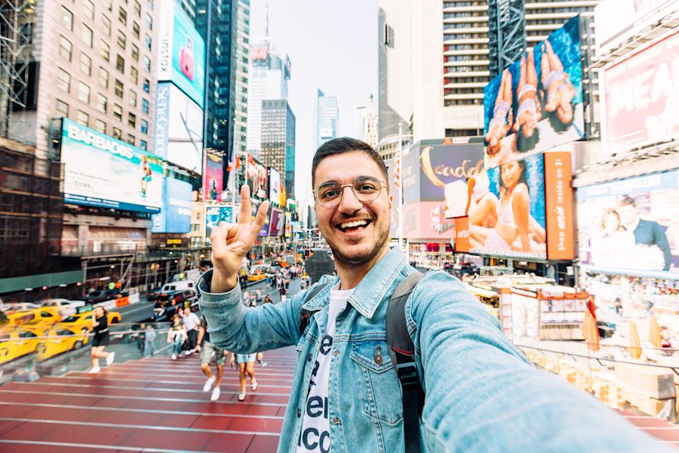 Young happy man taking selfie and showing peace gesture at Times Square, New York City, USA