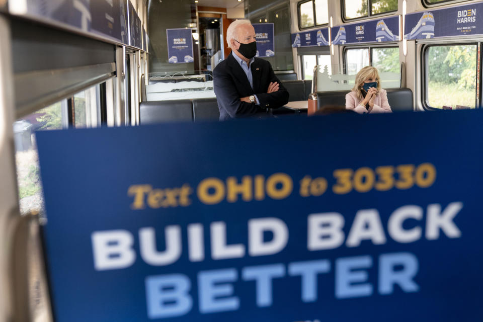 Democratic presidential candidate former Vice President Joe Biden and his wife Jill Biden, right, speak with invited guests aboard an Amtrak train, Wednesday, Sept. 30, 2020, as it makes its way to Alliance, Ohio. Biden is on a train tour through Ohio and Pennsylvania today. (AP Photo/Andrew Harnik)