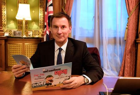 "Britain's Foreign Secretary Jeremy Hunt is seen with a copy of ""Jay Jay the Journalist"" written by Wa Lone, one of two Reuters reporters currently imprisoned in Myanmar, whilst working in his office in London, Britain, December 20, 2018. REUTERS/Toby Melville"