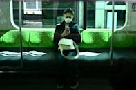 A woman uses her phone on the Yamanote Line train in Tokyo on the first day of the state of emergency