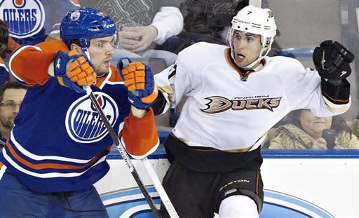 Anaheim Ducks Andrew Cogliano, right, is checked by Edmonton Oilers Mark Fistric during second period NHL hockey action in Edmonton, Alberta, on Sunday April 21, 2013. (AP Photo/The Canadian Press, Jason Franson)