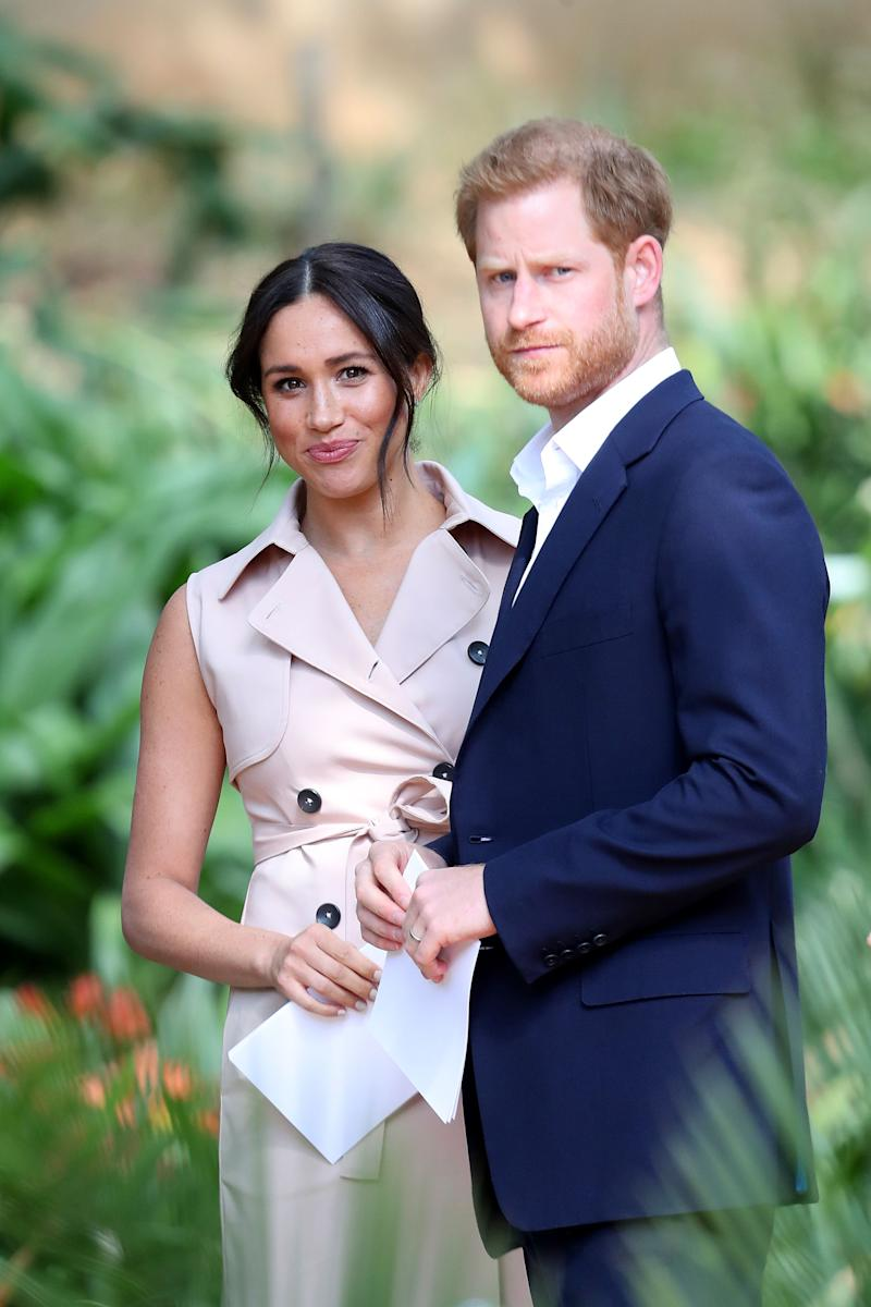 Meghan Markle (LEft) and Prince Harry (right) stand together holding sheets of paper